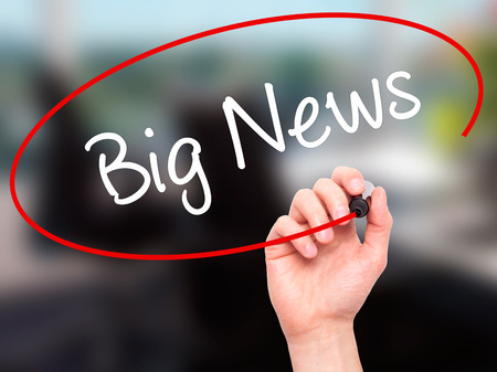annoucement: Man Hand writing Big News with black marker on visual screen. Isolated on office. Business, technology, internet concept. Stock Photo
