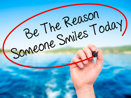 someone: Man Hand writing Be The Reason Someone Smiles Today  with black marker on visual screen. Isolated on nature. Business, technology, internet concept. Stock Photo