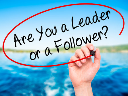 blindly: Man Hand writing Are You a Leader or a Follower? with black marker on visual screen. Isolated on nature. Business, technology, internet concept. Stock Photo Stock Photo