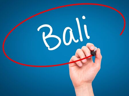 bali province: Man Hand writing Bali  with black marker on visual screen. Isolated on blue. Business, technology, internet concept. Stock Photo Stock Photo