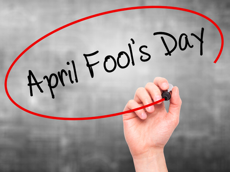 Man Hand writing April Fool's Day with black marker on visual screen. Isolated on grey. Business, technology, internet concept. Stock Photo
