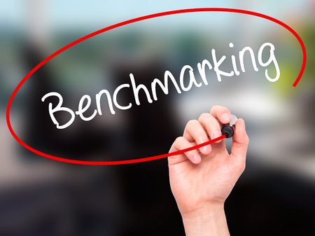benchmarking: Man Hand writing Benchmarking  with black marker on visual screen. Isolated on office. Business, technology, internet concept. Stock Photo