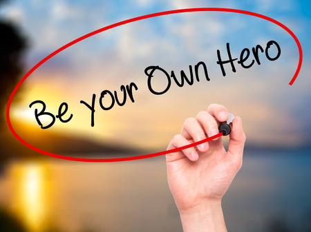 father in law: Man Hand writing  Be your Own Hero  with black marker on visual screen. Isolated on nature. Business, technology, internet concept. Stock Photo