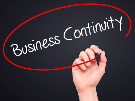 drp: Man Hand writing Business Continuity with black marker on visual screen. Isolated on black. Business, technology, internet concept. Stock Photo