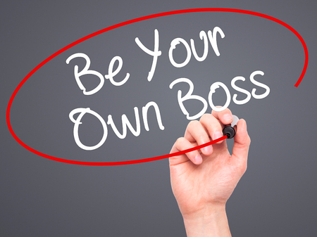 self starter: Man Hand writing Be Your Own Boss with black marker on visual screen. Isolated on grey. Business, technology, internet concept. Stock Image Stock Photo