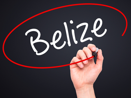 tourism in belize: Man Hand writing Belize with black marker on visual screen. Isolated on black. Business, technology, internet concept. Stock Photo