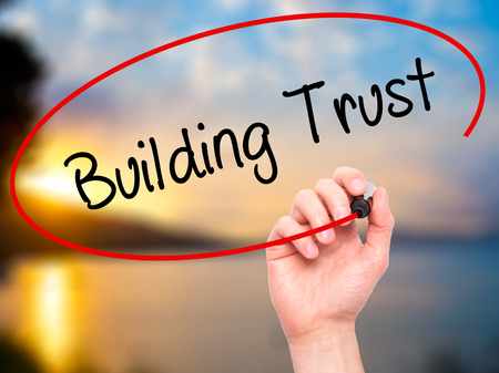 building trust: Man Hand writing Building Trust with black marker on visual screen. Isolated on background. Business, technology, internet concept. Stock Photo