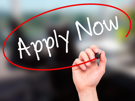 e recruitment: Man Hand writing Apply Now with black marker on visual screen. Isolated on office. Business, technology, internet concept. Stock Photo