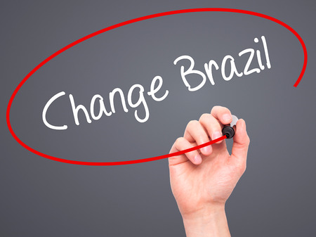 protestors: Man Hand writing Change Brazil  with black marker on visual screen. Isolated on grey. Business, technology, internet concept. Stock Photo