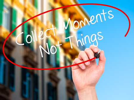 self discovery: Man Hand writing Collect Moments Not Things with black marker on visual screen. Isolated on city. Business, technology, internet concept. Stock Photo Stock Photo