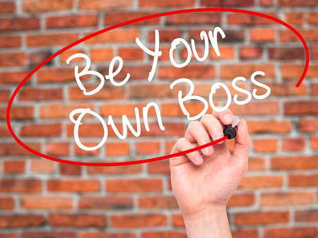 self starter: Man Hand writing Be Your Own Boss with black marker on visual screen. Isolated on bricks. Business, technology, internet concept. Stock Image Stock Photo