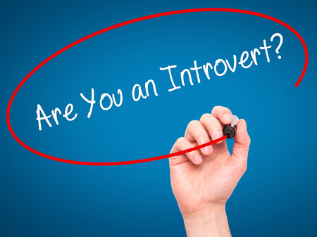 introvert: Man Hand writing Are You an Introvert? with black marker on visual screen. Isolated on blue. Business, technology, internet concept. Stock Photo