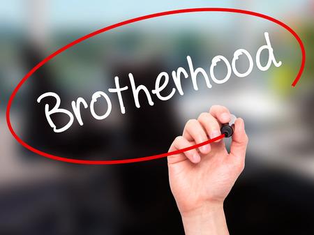 fraternidad: Hombre de la mano escribiendo Hermandad con marcador negro en la pantalla visual. Aislado en el fondo. Negocios, la tecnolog�a, el concepto de internet. Foto de stock Foto de archivo