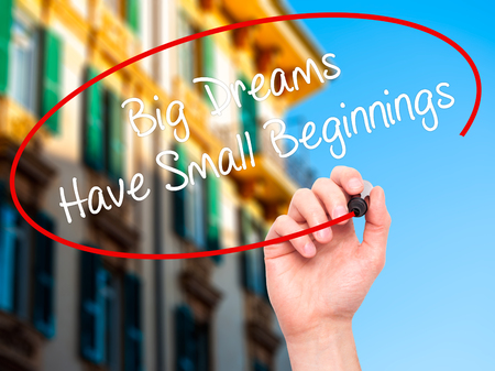 dreams of city: Man Hand writing Big Dreams Have Small Beginnings with black marker on visual screen. Isolated on city. Business, technology, internet concept. Stock Photo