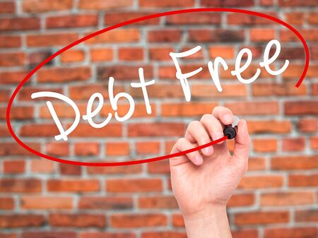 Man Hand writing Debt Free with black marker on visual screen. Isolated on bricks. Business, technology, internet concept. Stock Photo