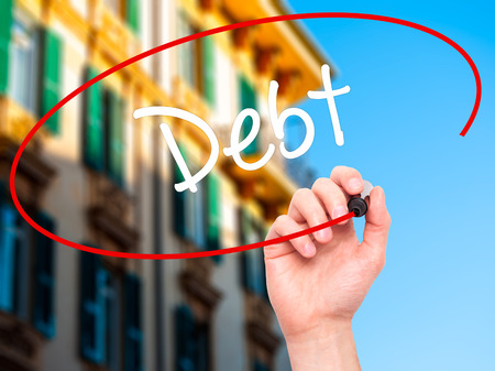 creditors: Man Hand writing Debt with black marker on visual screen. Isolated on city. Business, technology, internet concept.