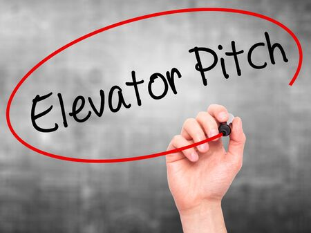 business pitch: Man Hand writing Elevator Pitch with black marker on visual screen. Isolated on grey. Business, technology, internet concept. Stock Photo