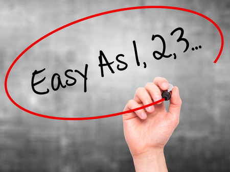 Man Hand writing Easy As 1,2,3... with black marker on visual screen. Isolated on grey. Business, technology, internet concept. Stock Photo