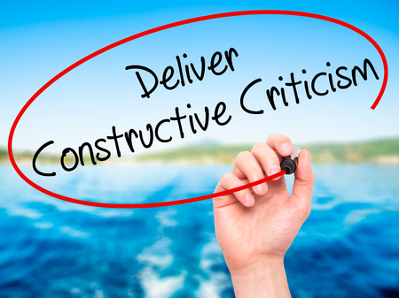 constructive: Man Hand writing Deliver Constructive Criticism with black marker on visual screen. Isolated on background. Business, technology, internet concept. Stock Photo