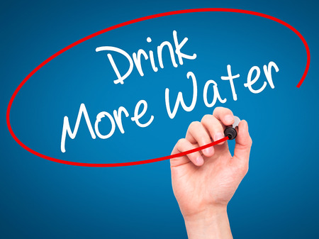 living wisdom: Man Hand writing Drink More Water with black marker on visual screen. Isolated on blue. Business, technology, internet concept. Stock Photo