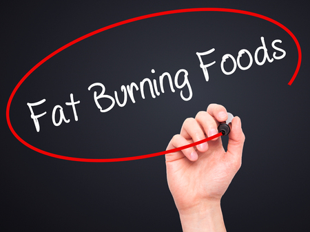 fat burning: Man Hand writing Fat Burning Foods with black marker on visual screen. Isolated on black. Business, technology, internet concept. Stock Photo