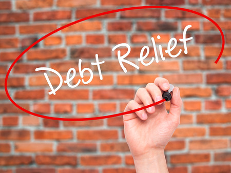 consolidation: Man Hand writing Debt Relief with black marker on visual screen. Isolated on bricks. Business, technology, internet concept. Stock Photo Stock Photo