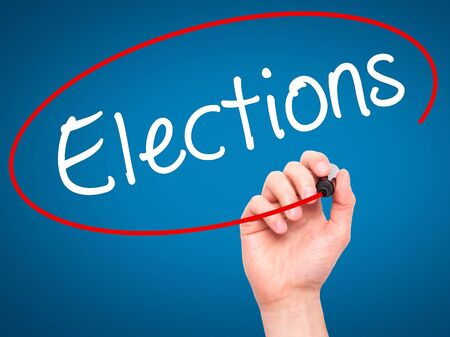 nomination: Man Hand writing Elections with black marker on visual screen. Isolated on blue. Business, technology, internet concept. Stock Image