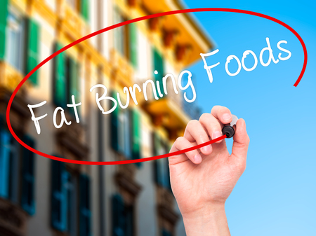 fat burning: Man Hand writing Fat Burning Foods with black marker on visual screen. Isolated on city. Business, technology, internet concept. Stock Photo