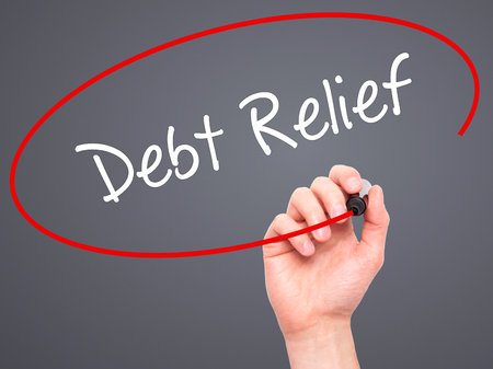 trouble free: Man Hand writing Debt Relief with black marker on visual screen. Isolated on grey. Business, technology, internet concept. Stock Photo Stock Photo