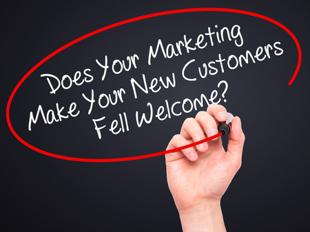does: Man Hand writing Does Your Marketing Make Your New Customers Fell Welcome?  with black marker on visual screen. Isolated on white. Business, technology, internet concept. Stock Photo Stock Photo