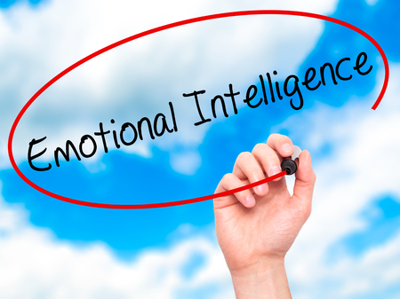 continence: Man Hand writing Emotional Intelligence with black marker on visual screen. Isolated on sky. Business, technology, internet concept. Stock Photo Stock Photo