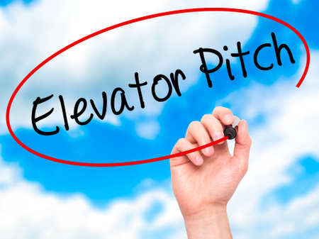 business pitch: Man Hand writing Elevator Pitch with black marker on visual screen. Isolated on sky. Business, technology, internet concept. Stock Photo Stock Photo