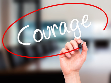 unafraid: Man Hand writing Courage with black marker on visual screen. Isolated on background. Business, technology, internet concept. Stock Photo