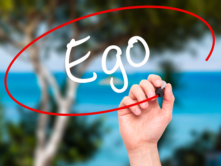 ego: Man Hand writing Ego with black marker on visual screen. Isolated on background. Business, technology, internet concept. Stock Photo