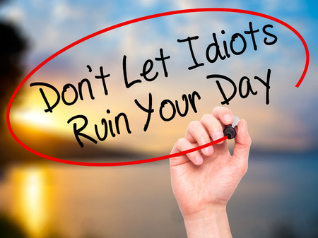 irrelevant: Man Hand writing Dont Let Idiots Ruin Your Day with black marker on visual screen. Isolated on nature. Business, technology, internet concept. Stock Photo
