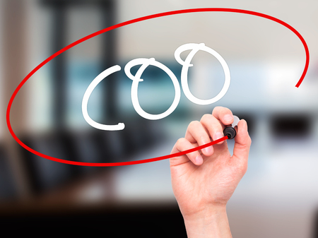 coo: Man Hand writing COO (Chief Operating Officer) with black marker on visual screen. Isolated on background. Business, technology, internet concept. Stock Photo