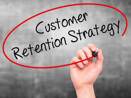 retention: Man Hand writing Customer Retention Strategy with black marker on visual screen. Isolated on grey. Business, technology, internet concept.