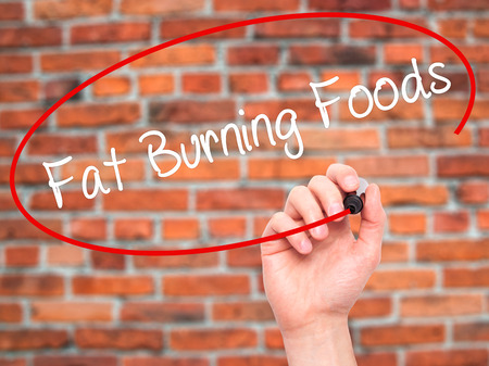 fat burning: Man Hand writing Fat Burning Foods with black marker on visual screen. Isolated on bricks. Business, technology, internet concept. Stock Photo
