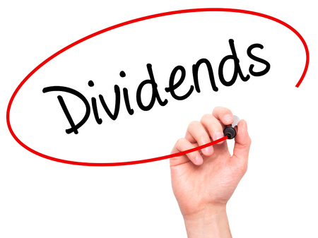 Man Hand writing Dividends with black marker on visual screen. Isolated on background. Business, technology, internet concept. Stock Photo