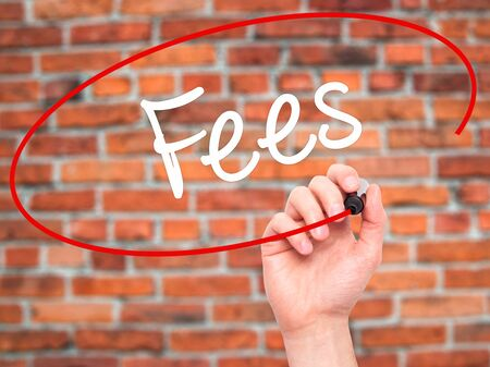 hidden costs: Man Hand writing Fees with black marker on visual screen. Isolated on background. Business, technology, internet concept. Stock Photo
