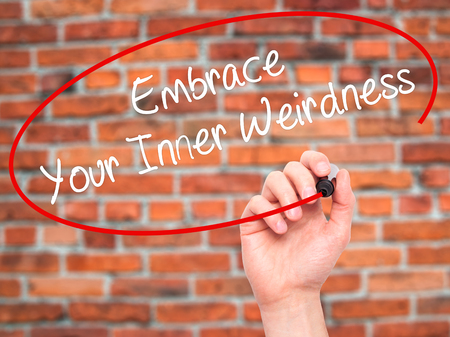 street wise: Man Hand writing Embrace Your Inner Weirdness  with black marker on visual screen. Isolated on bricks. Business, technology, internet concept. Stock Photo Stock Photo