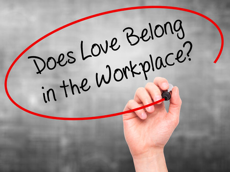 belong: Man Hand writing Does Love Belong in the Workplace? with black marker on visual screen. Isolated on grey. Business, technology, internet concept. Stock Photo Stock Photo