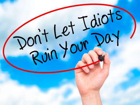 stupidity: Man Hand writing Dont Let Idiots Ruin Your Day with black marker on visual screen. Isolated on sky. Business, technology, internet concept. Stock Photo