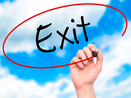 exiting: Man Hand writing Exit with black marker on visual screen. Isolated on background. Business, technology, internet concept. Stock Photo