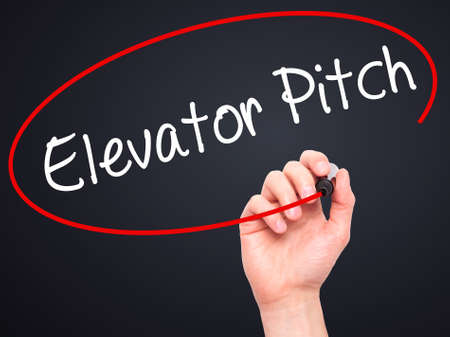 business pitch: Man Hand writing Elevator Pitch with black marker on visual screen. Isolated on black. Business, technology, internet concept. Stock Photo Stock Photo