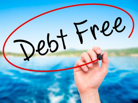 Man Hand writing Debt Free with black marker on visual screen. Isolated on nature. Business, technology, internet concept. Stock Photo