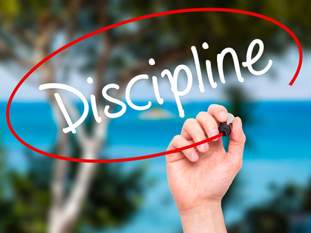 disciplined: Man Hand writing Discipline with black marker on visual screen. Isolated on nature. Business, technology, internet concept. Stock Photo Stock Photo