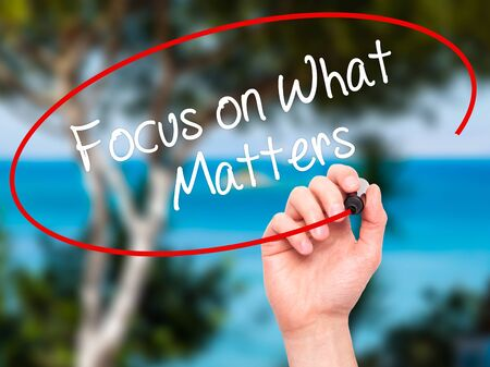 objectivism: Man Hand writing Focus on What Matters with black marker on visual screen. Isolated on nature. Business, technology, internet concept. Stock Photo Stock Photo