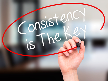 consistency: Man Hand writing Consistency is The Key with black marker on visual screen. Isolated on office. Business, technology, internet concept. Stock Photo Stock Photo