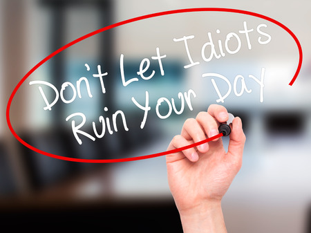 naivety: Man Hand writing Dont Let Idiots Ruin Your Day with black marker on visual screen. Isolated on office. Business, technology, internet concept. Stock Photo